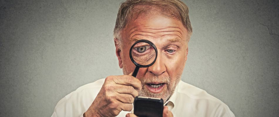 Anziano con cataratta che guarda un cellulare